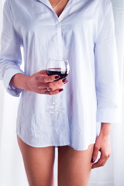 Girl in a shirt with a glass of red wine Premium Photo