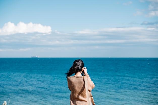 Girl shoot photo of sea Free Photo