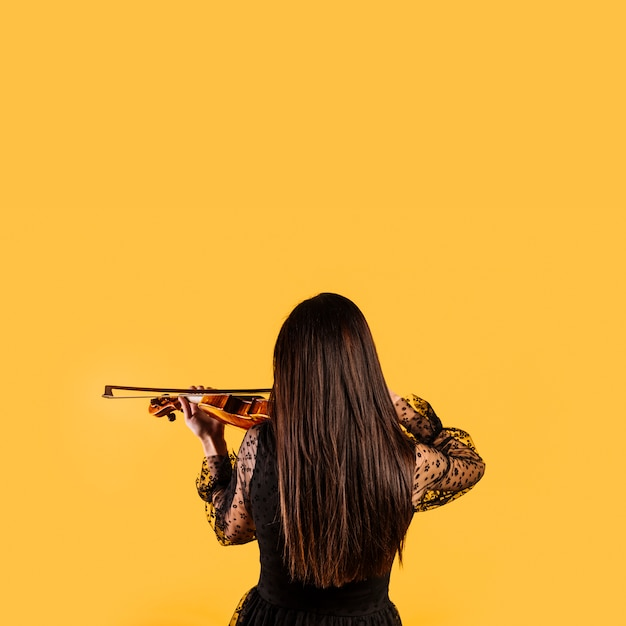 Girl showing her back playing the violin Free Photo
