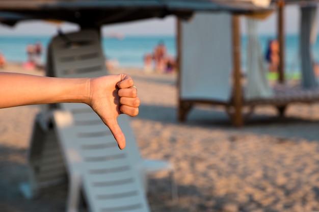 海、ビーチに親指を下に向けて嫌いな女の子 Premium写真