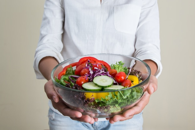Girl showing her salad with cherry tomatoes and cucumbers Free Photo