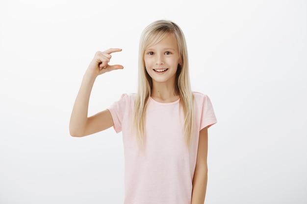 幸せになるためにどれだけの労力がかかるかを示している女の子。ピンクのtシャツを着た明るくフレンドリーな金髪の女性の子供の屋内ショット 無料写真