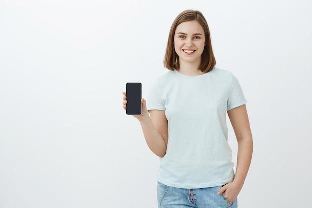 Девушка показывает новый телефон, купленный родителями к новому учебному семестру. восхищенная и довольная очаровательная молодая женщина показывает экран смартфона и рассказывает о крутом приложении, которое она нашла в интернет-магазине над серой стеной Бесплатные Фотографии