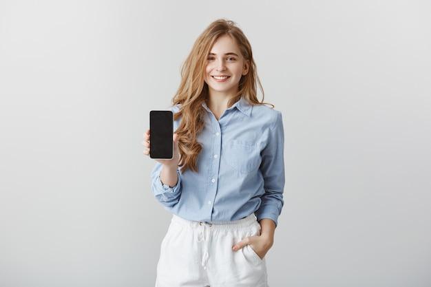 동료에 게 새 전화를 보여주는 소녀. 공식적인 파란색 블라우스에 매력적인 친근한 유럽 패션 블로거의 초상화, 회색 벽 위에 스마트 폰을 보여주는 동안 주머니에 손을 잡고 광고 무료 사진