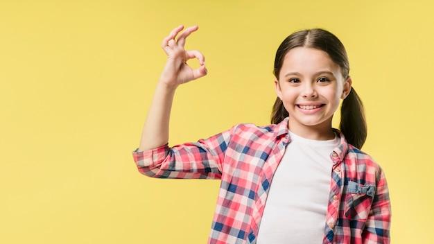 Girl showing okay sign in studio Free Photo