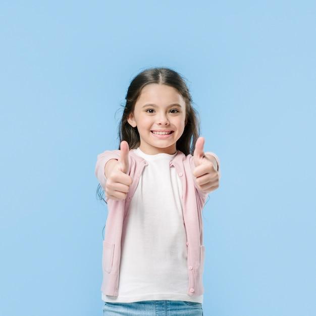 Girl showing thumbs in studio Free Photo
