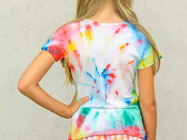 The girl shows the back of a t-shirt, painted in the style of tie dye. Premium Photo