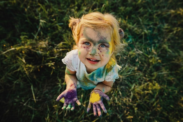 Girl shows her little palms covered with colorful paints Free Photo