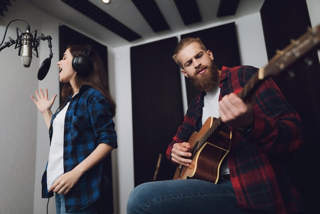 Girl sings, and the guy plays the guitar. Premium Photo