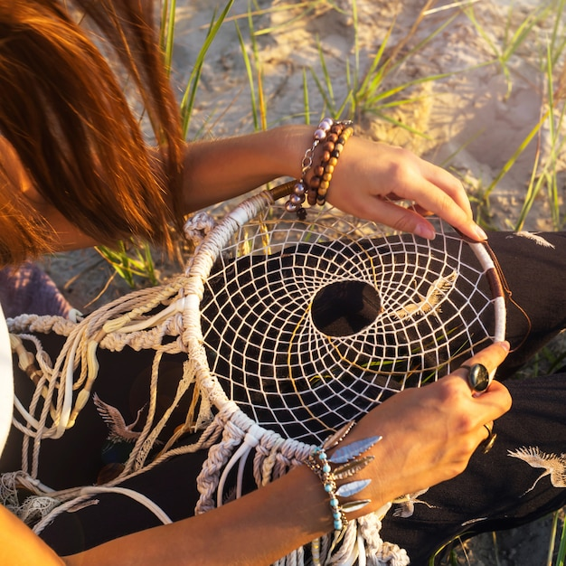 A Girl Sits On The Grass And Holds A Dream Catcher Photo