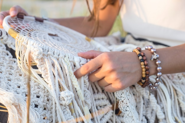 A girl sits on the grass and holds a dream catcher Premium Photo