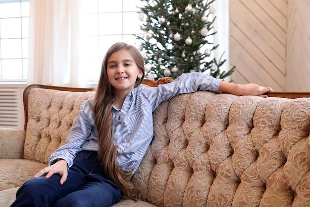 女の子はソファに座っています 無料写真