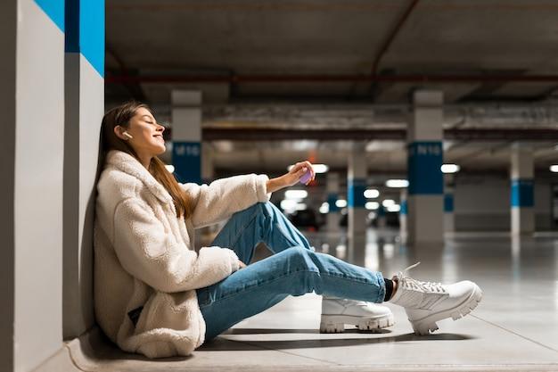 女の子は地下駐車場の床に座っています Premium写真