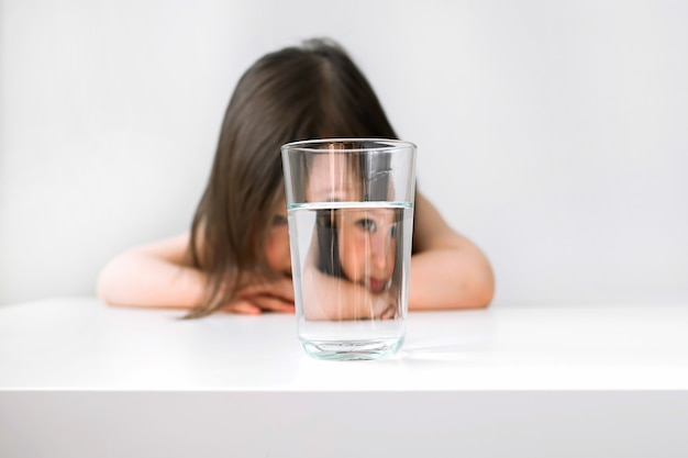 The girl sits at the table upset. the girl is sad because she does not want to drink water. Premium Photo