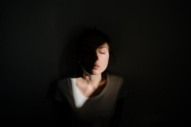 Girl sitting alone in sunlight pocket in dark room. mental health concept Premium Photo