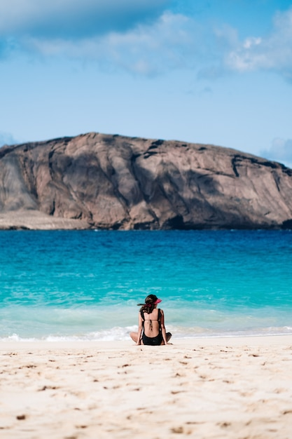 Girl sitting on the beach watching the sea Premium Photo