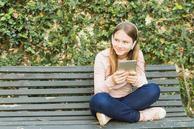 Girl sitting on bench holding mobile phone listening music on headphone Free Photo