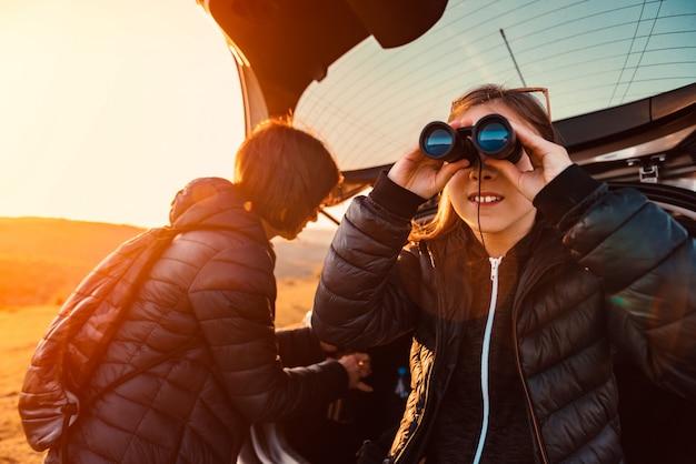 Girl sitting on a car trunk and using binoculars Premium Photo