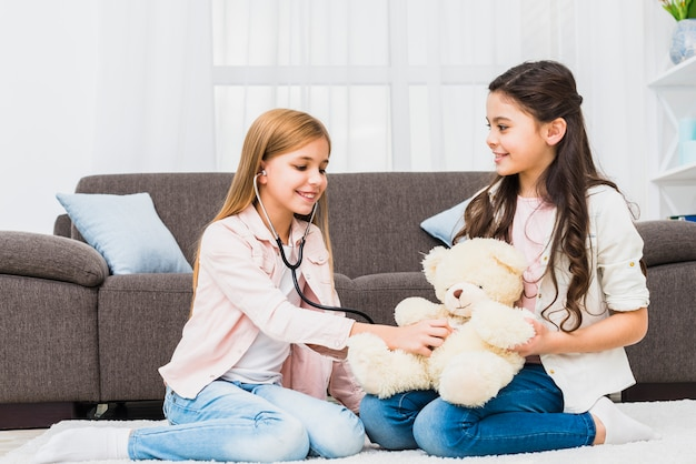 Girl sitting on carpet playing with teddy using stethoscope in the living room Free Photo