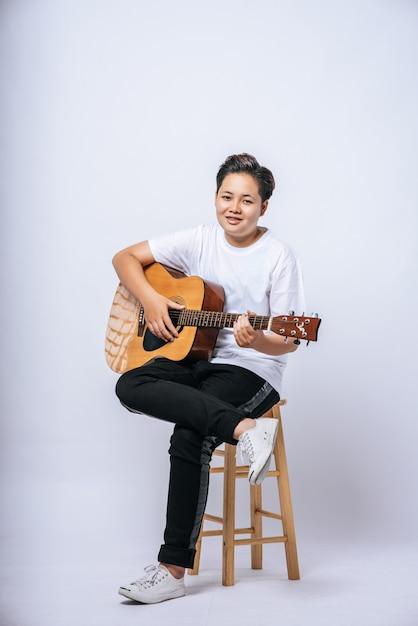 Ragazza seduta su una sedia e suonare la chitarra. Foto Gratuite