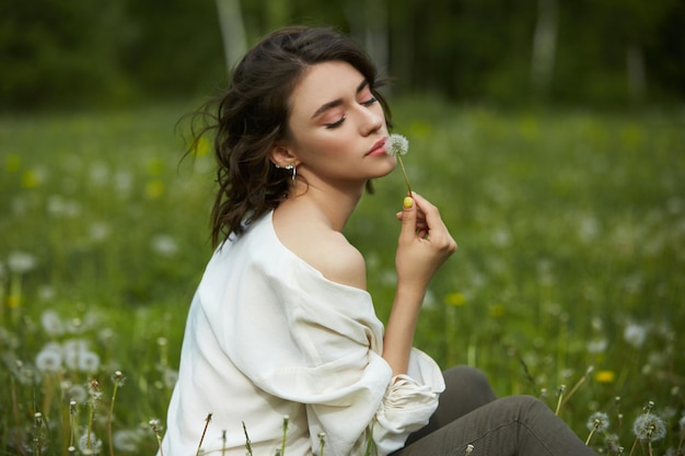 Girl sitting in a field on the spring grass with dandelion flowers Premium Photo