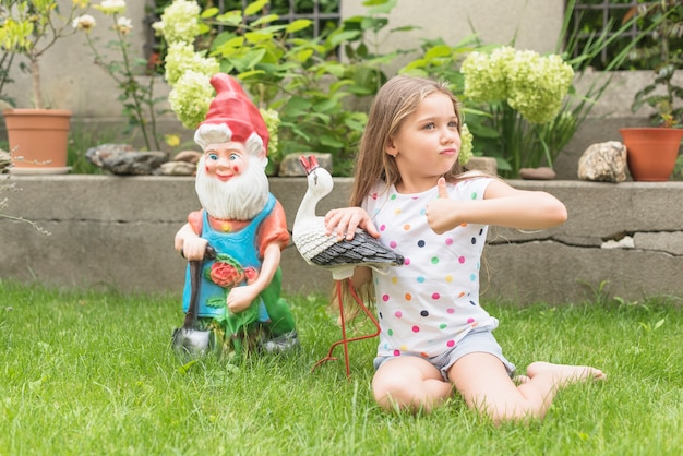 Girl sitting in the garden showing thumb up sign Free Photo