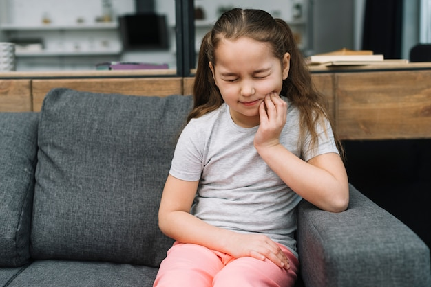 Girl sitting on gray sofa suffering from toothache Free Photo