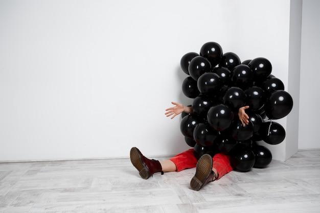 흰 벽 위에 손을 스트레칭 검은 Baloons에 앉아 소녀. 무료 사진