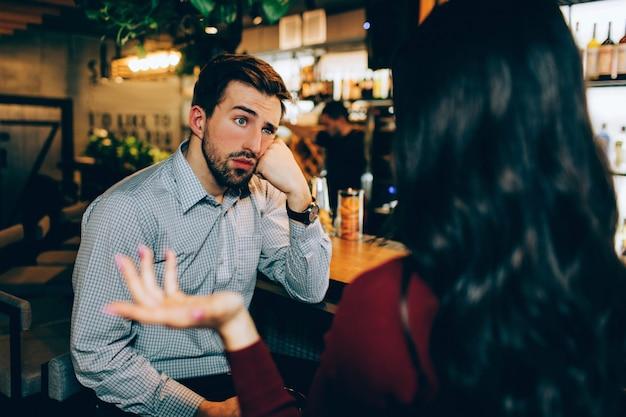 Девушка сидит перед молодым парнем и разговаривает с ним Premium Фотографии
