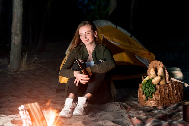 Girl sitting and looking at bonfire Free Photo