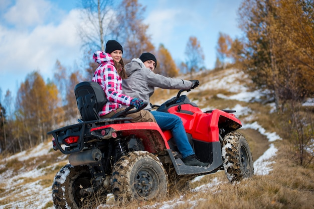 Girl sitting behind man hugging him on red four-wheeler atv and looking to the camera at snowy hill in the mountains Premium Photo