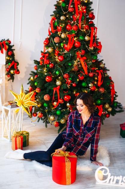 クリスマスツリーと素晴らしい贈り物の近くの床に座って横を見る女の子 Premium写真