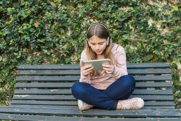 Girl sitting on bench wearing headphone using mobile phone in park Free Photo