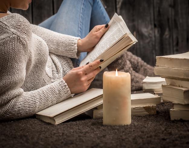多くの白い本と大きなキャンドルに囲まれた床に座っている女の子 無料写真