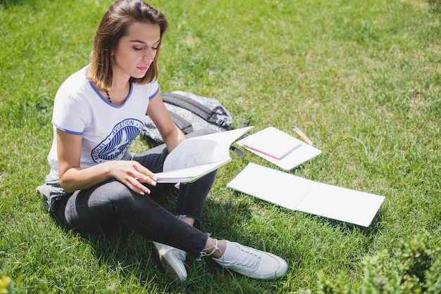 Girl sitting in park holding notebook reading Free Photo