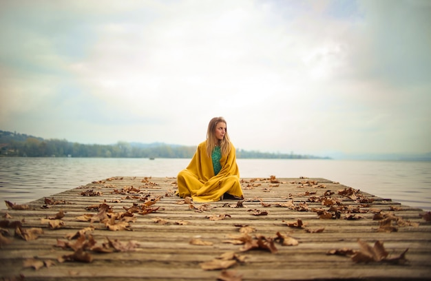 Girl sitting on a pier, looking the horizon Premium Photo