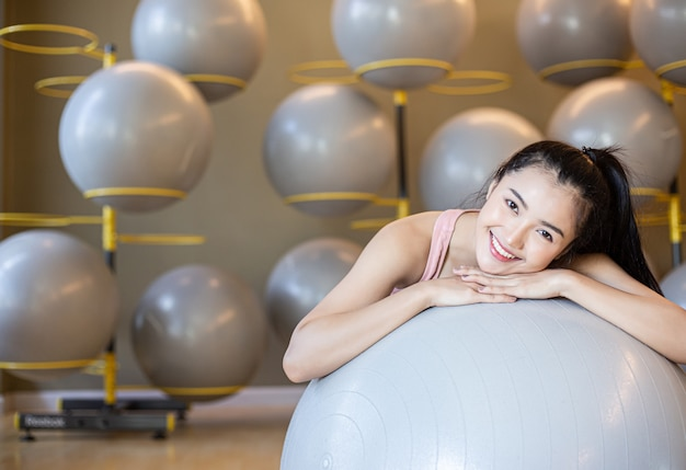 The girl sitting relax with the ball in the gym. Free Photo