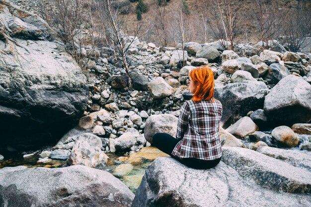 The girl sitting on the rock mountain Premium Photo