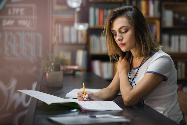 Girl sitting at table with notebooks writing Premium Photo