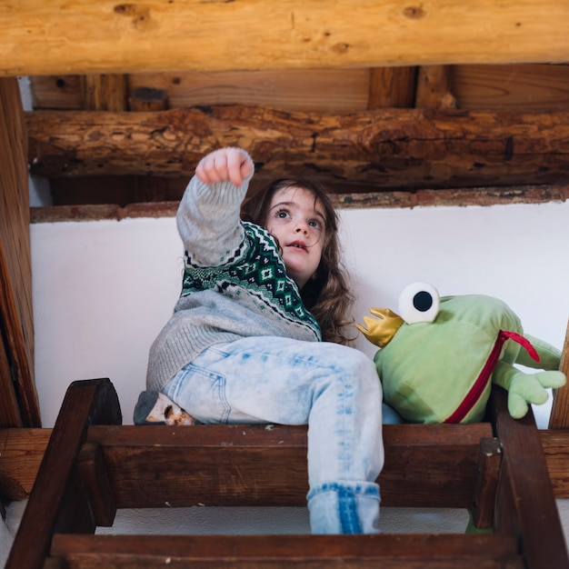 Girl sitting on top of the staircase with soft toy Free Photo