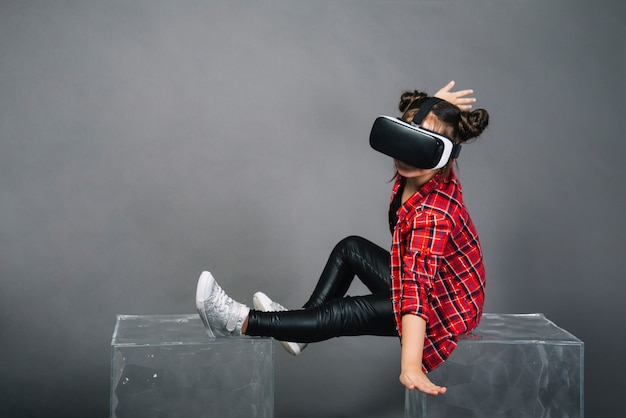 Girl sitting on transparent blocks wearing virtual reality goggles against gray background Free Photo