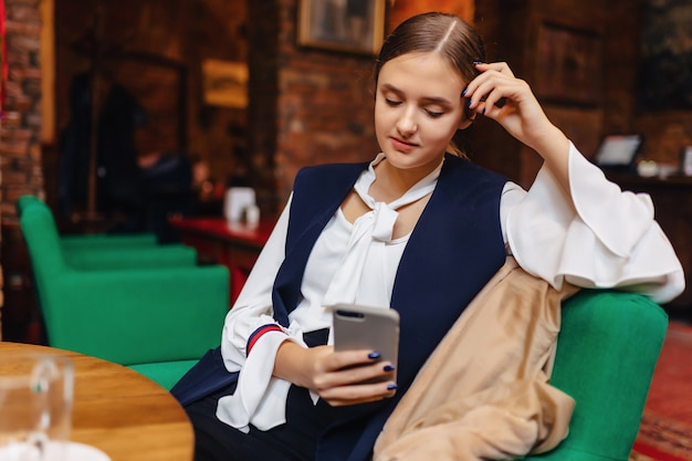 Girl sitting with phone in cafe Premium Photo