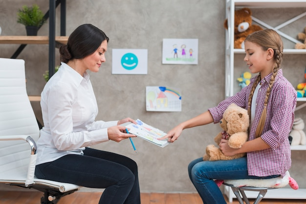 Girl sitting with teddy bear pointing at the drawing paper shown by her female psychologist Free Photo