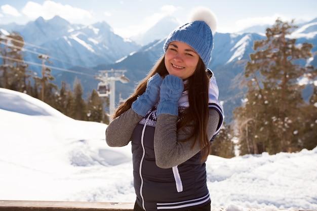 スキーリゾートのカフェのベランダのインテリアでポーズをとって丘の上の少女スキーヤー Premium写真