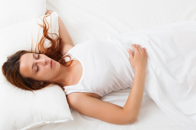 girl sleeping on a white pillow in bed at home Free Photo