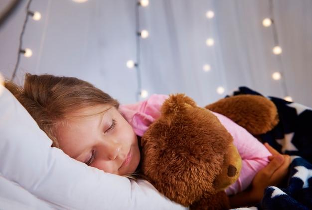 彼女の寝室でテディベアと一緒に寝ている女の子 無料写真