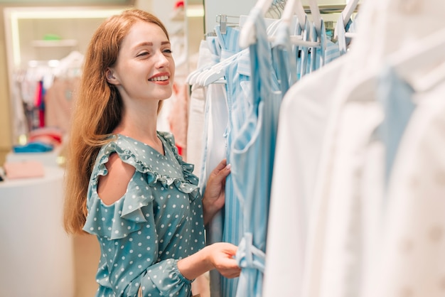 Girl smiling and checking clothes Free Photo