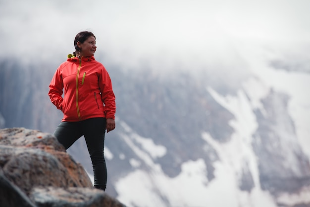 Girl smiling in a red jacket, standing on the mountain. Premium Photo