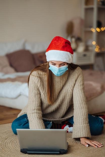 집에서 크리스마스 축하 기간 동안 노트북에 온라인 친구와 이야기하는 동안 웃는 소녀. 코로나 바이러스 제한에 따라 새해와 크리스마스를 축하하는 개념. 방역 휴가 무료 사진
