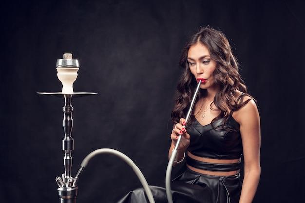 Girl smokes hookah / beautiful glamorous girl in black dress smokes a hookah Premium Photo